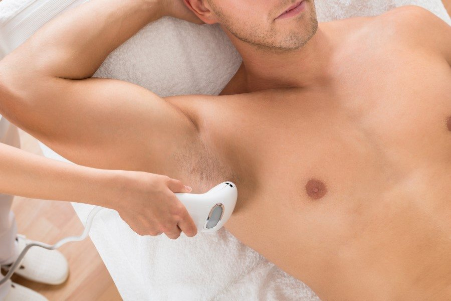 Man receiving laser hair removal treatment on chest and underarm