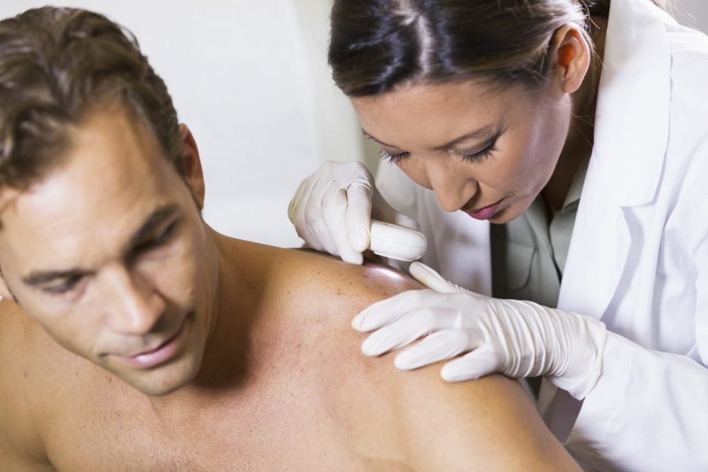 Dermatologist examining a mole on a male patient's shoulder