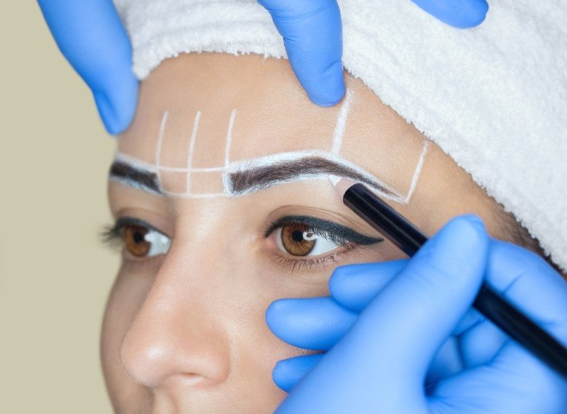 Woman getting permanent eyebrows cosmetic procedure