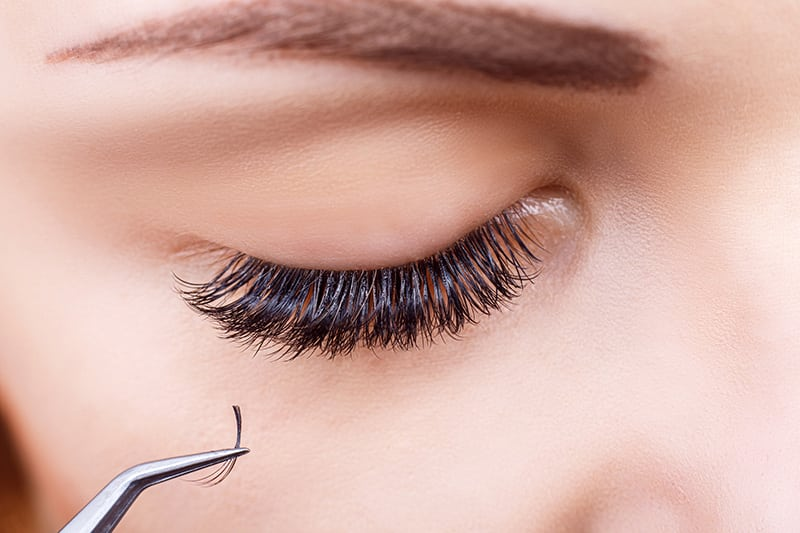 Closeup of Eyelash Extensions Being Applied to a Woman's Eye
