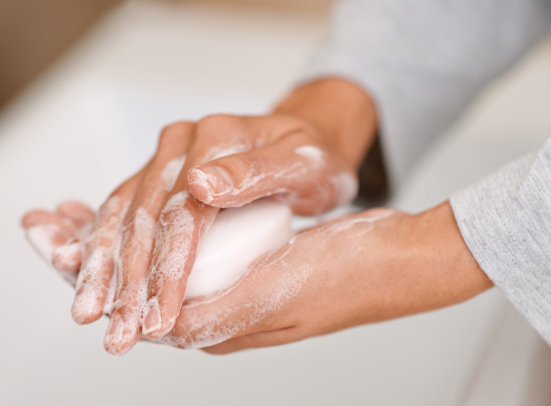 Person washing their hands with a bar of soap