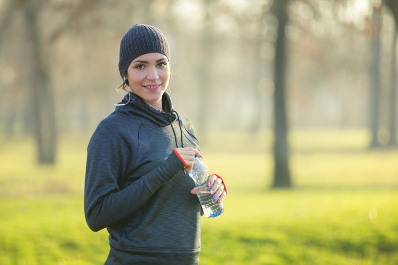 Woman outdoors walking with water bottle