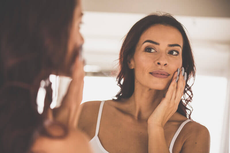 Healthy Skincare - Woman Looking at Her Skin in the mirror