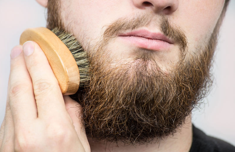Man Applying Beard Balm with Boar Bristle Brush