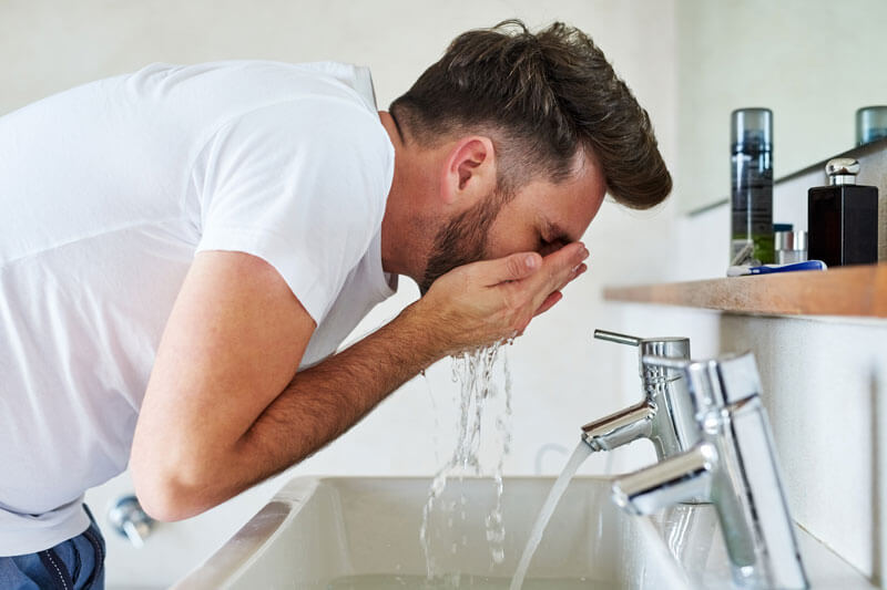 Man Washing his Face and Beard
