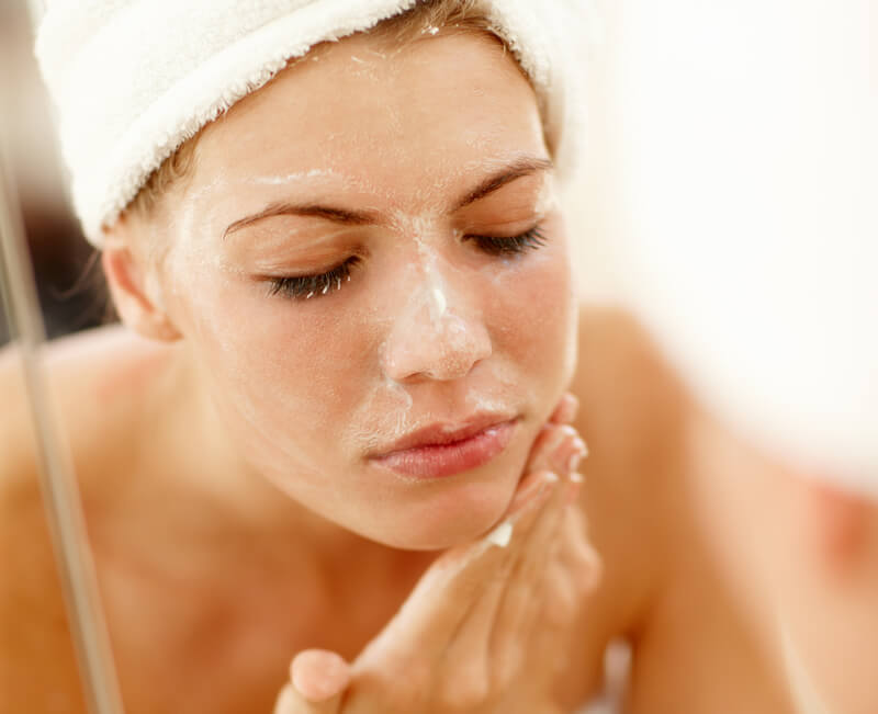 Woman Cleaning and Exfoliating Her Skin