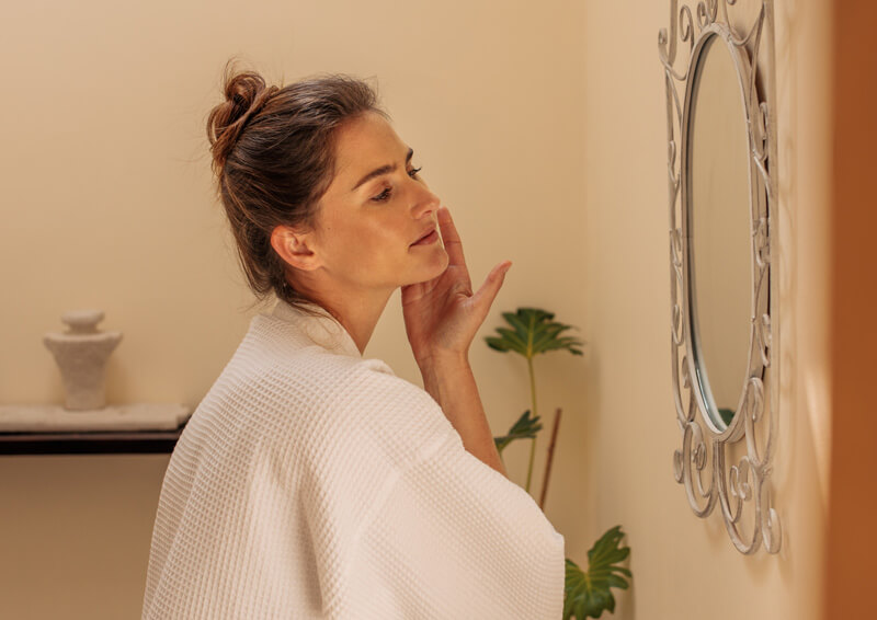 Woman Using Moisturizer on Her Face