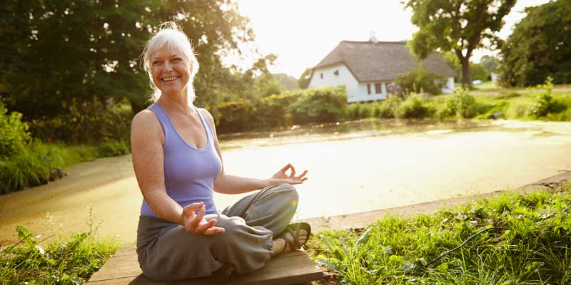 Attractive mature woman meditating in a garden at sunset, meditation-changes-appearance