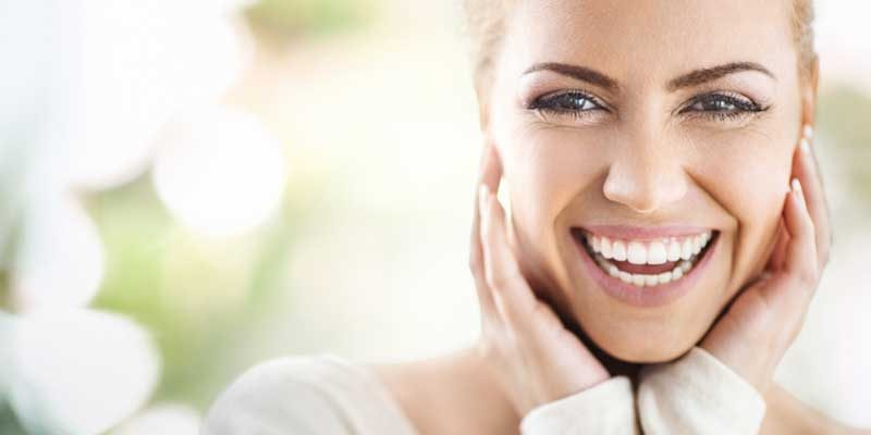 Closeup portrait of an attractive mid 30's woman gently touching her neck and with a glowing smile, meditation-a-glow-from-within