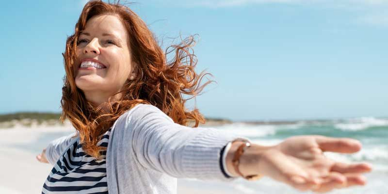 Beautiful middle aged woman with red hair and arms up dancing on beach in summer during holiday, meditation-changes-your-appearance